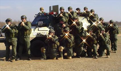 A group photo of a SWAT team standing in front of their vehicle.