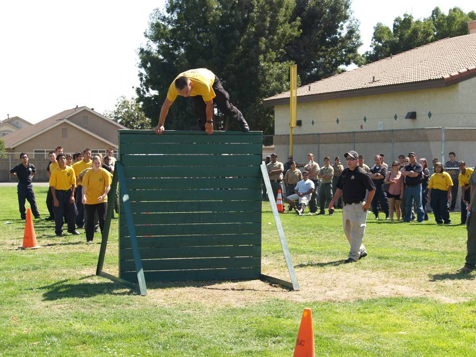 People going over a wall as part of an obstacle course.