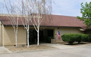Merced Office Image of one story tan building with American flag at entrance