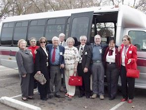 Group of senior citizens standing in front of a bus in a parking lot