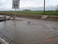 Image of flooded road with caution barriers