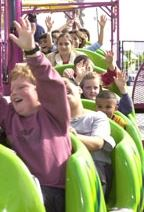 Children raise hands on wacky worm ride