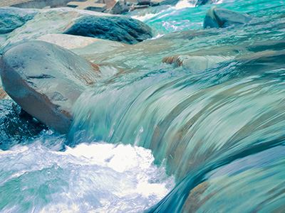 Turquoise Water Flowing Rapidly Over Riverbed Stones