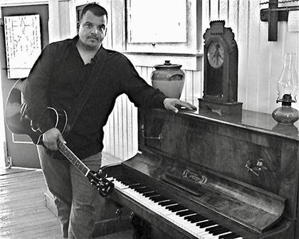 Black-and-White Photo of Musician Aaron-Avila Holding Guitar Next to Piano