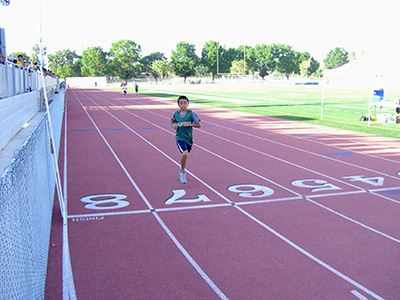 Boy Crossing Lap Line on Track
