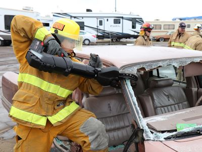 Fireman with Jaws of Life Dismantling Car