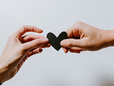 Hands Holding a Black Paper Heart